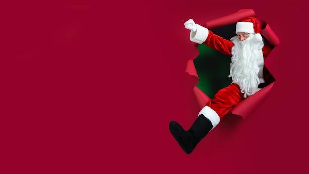 Santa człowiek idący przez dziurę w papierze jak super człowiek