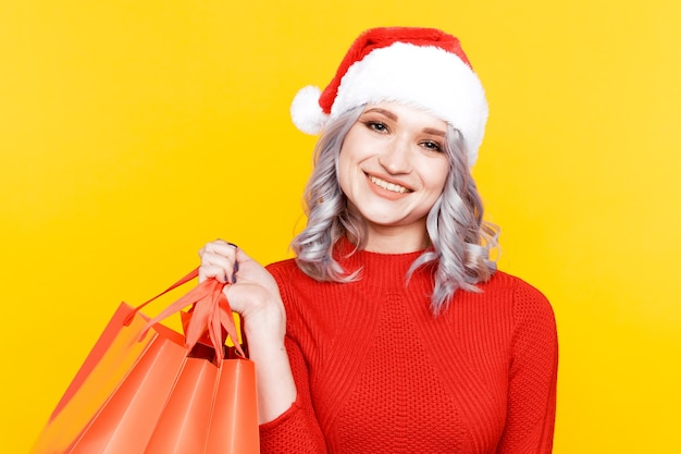 Santa dziewczyna w kapeluszu, trzymając duże torby z prezentami na białym tle w żółtej ścianie