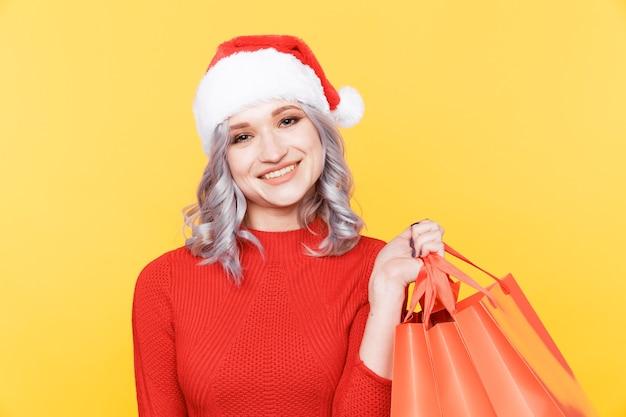 Santa dziewczyna w kapeluszu, trzymając duże torby z prezentami na białym tle w żółtym pokoju.