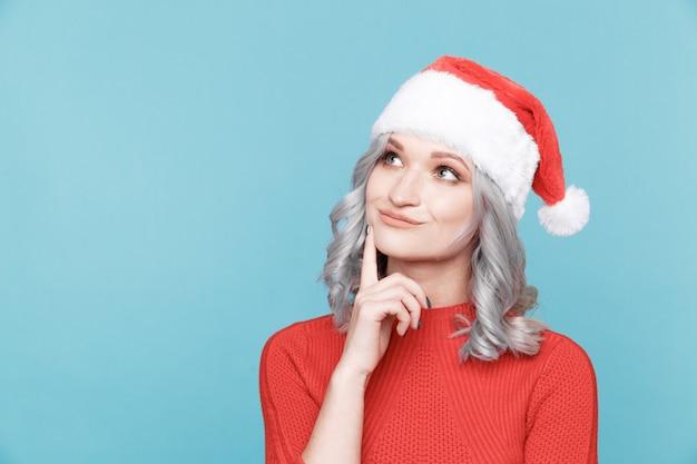 Santa dziewczyna w myśleniu poza na białym tle w niebieskim pokoju.