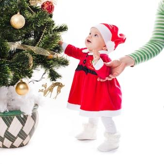 Santa dziewczynka w sukience obok choinki z ręką matki - moje pierwsze wakacje