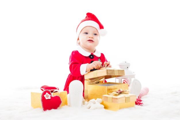 Santa dziewczynka z pudełkiem prezentowym i ozdobami świątecznymi na futerku