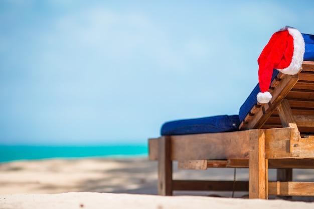 Santa hat na leżaku na plaży. koncepcja świąt bożego narodzenia