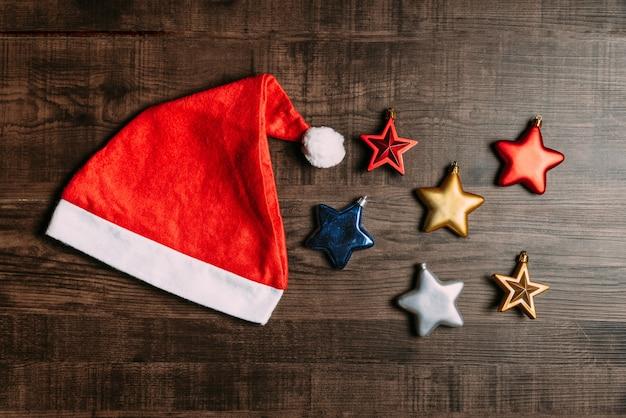 Santa kapelusz z kruszcowymi gwiazdami na drewnianym tle.