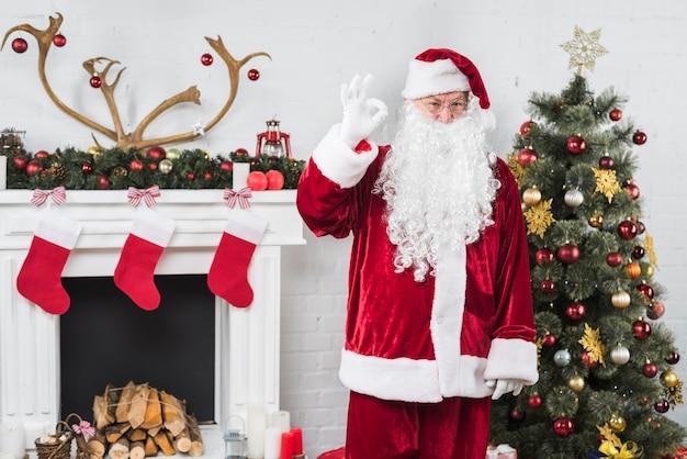 Santa pokazuje ok gestu blisko dekorującego kominka