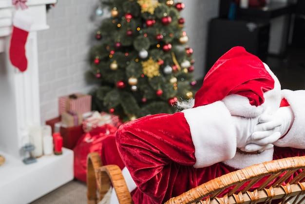 Santa siedzi na bujanym fotelu z rękami za głową