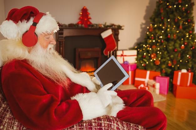 Santa słuchająca muzyka i wzruszająca pastylka