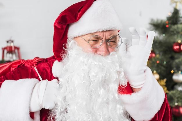 Santa w szkło blisko dekorującej choinki
