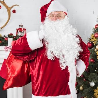 Santa z dużym workiem w pobliżu choinki