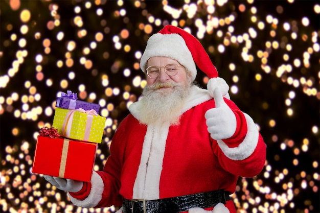 Santa z prezentami pokazuje kciuk w górę.