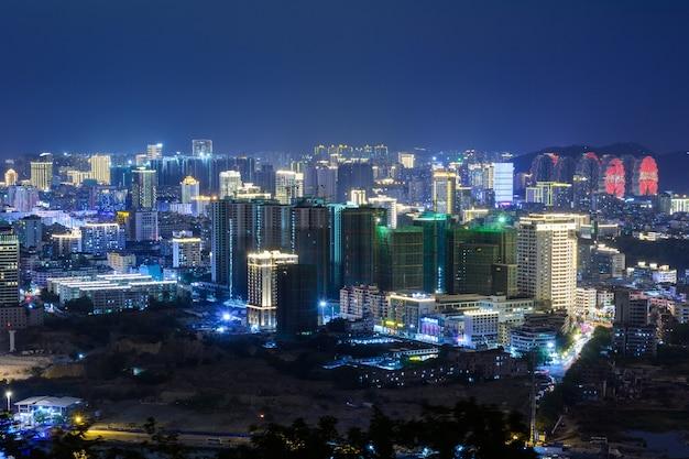 Sanya/chiny - 01 kwietnia 2020 r.: nocny widok miasta sanya z jasnymi wielokolorowymi iluminacjami budynków, konstrukcji, dróg, chodników, słupów, mostów. hajnan.
