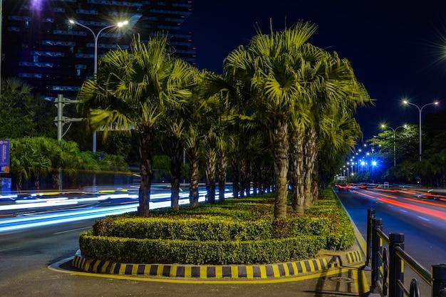 Sanya, hainan, chiny - 25 stycznia 2020: nocny widok miasta sanya z jasnymi wielokolorowymi iluminacjami budynków, konstrukcji, dróg, chodników, słupów, mostów.
