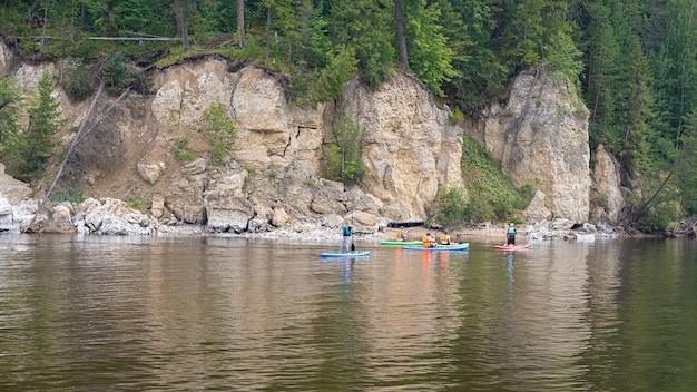 Sap surferzy wiosłują po rzece wzdłuż klifów i cieszą się widokiem