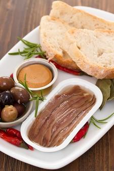 Sardele, oliwki, chleb i pasztet rybny na talerzu