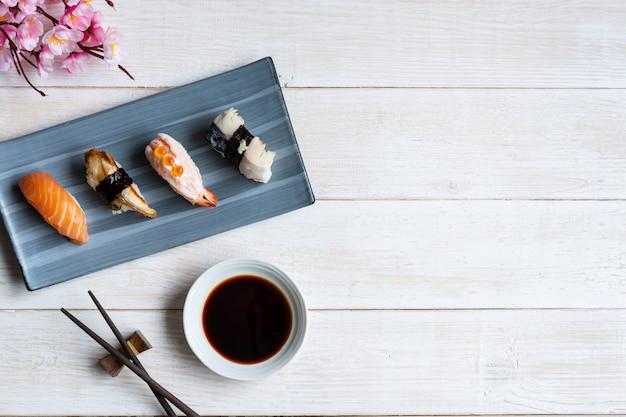 Sashimi sushi zestaw z sosem sojowym na białym drewnianym stole, widok z góry