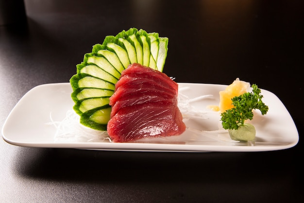 Sashimi z tuńczykiem w białym talerzu. na czarnym tle.