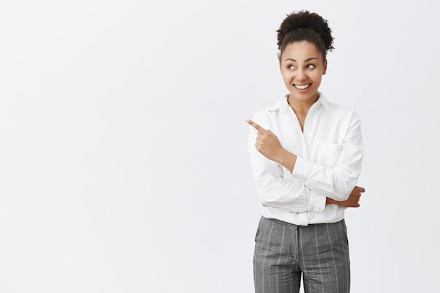 Sassy african american businesswoman pokazując sposób, wskazując lewy górny róg