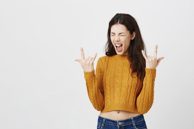 Sassy atrakcyjna brunetka dziewczyna pokazuje rock-n-roll gest, zabawy na koncercie