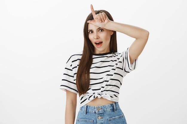 Sassy atrakcyjna dziewczyna kpiąca z drużyny, która przegrała, pokazując przegrany gest nad czołem