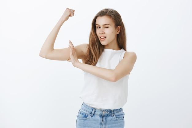 Sassy atrakcyjna dziewczyna trenuje na siłowni, napina bicepsy i mruga, zaprasza do kupna członkostwa, dołącz do zespołu fitness