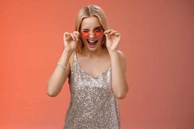 Sassy, beztroski, śmiała młoda blond dziewczyna mrugająca bezczelnie, uśmiechnięta asertywnie