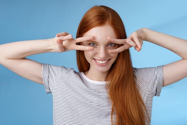 Sassy, buntownicza, zmysłowa, przystojna ruda dziewczyna niebieskie oczy uśmiechnięte bezczelnie okazywać znaki pokoju zwycięstwo uśmiechnięte oczy zadowolona pewna siebie ekspresja pewna siebie pozytywna postawa, tło studyjne.