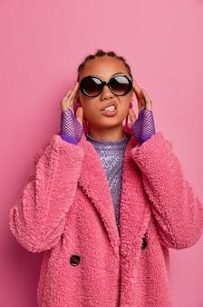 Sassy chic woman stoi z pewnym siebie wyrazem, zakłada modne odcienie, wygląda pewnie, ubrana w modne luksusowe ciuchy z ostatniej kolekcji, gotowa na imprezę lub randkę. styl uliczny