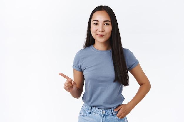 Sassy, dobrze wyglądająca, pewna siebie brunetka azjatycka kobieta udzielająca porad, jaki produkt wybrać, pokazująca najlepszy wybór, wskazująca w lewo, uśmiechnięta zadowolona dająca znające spojrzenie, trzymająca rękę w kieszeni dżinsów, biała ściana