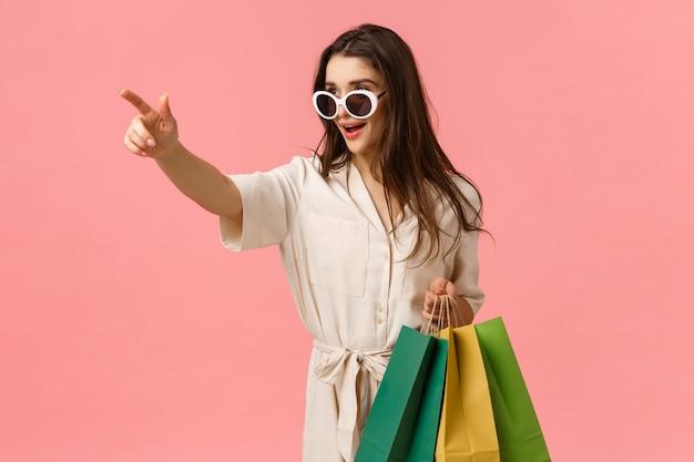 Sassy i elegancka młoda kobieta w sukience, widząca dokładnie to, czego potrzebuje, trzymająca torby na zakupy, wskazująca palcem bokiem i wyglądająca na zdeterminowaną, stojąca podekscytowana różowa ściana