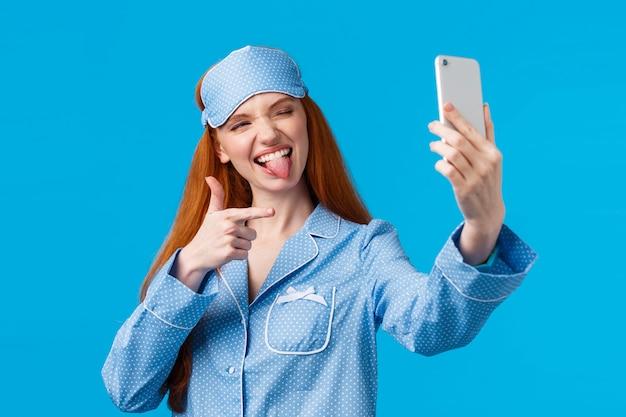 Sassy i popularna ruda blogerka robiąca transmisję na żywo z sypialni, rozmawiając o rutynie pielęgnacji i pielęgnacji skóry, robiąc selfie na telefonie, pokazując język i pistolet na palec