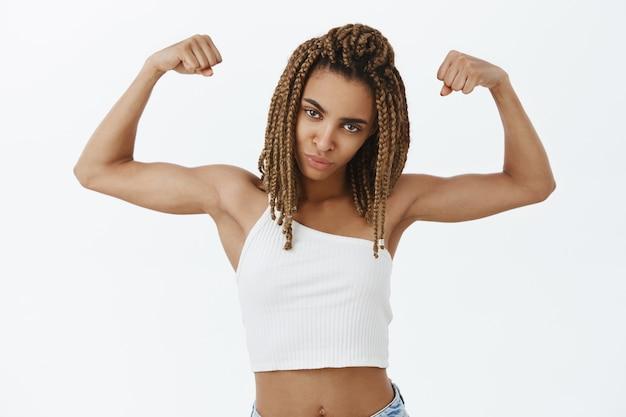 Sassy i silna afroamerykańska dziewczyna napinająca bicepsy, wyglądająca na pewną siebie