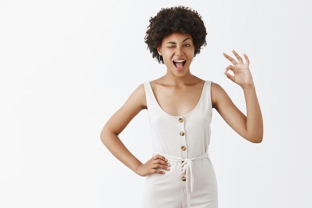 Sassy i szczęśliwa stylowa dziewczyna pozuje na białej ścianie