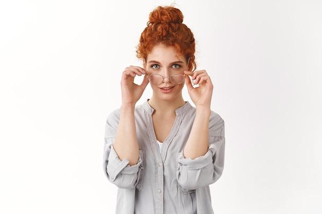 Sassy kobieca, kaukaska rudowłosa suczka z kręconymi włosami zaczesanymi w kok, w okularach przygotowana do pracy, wymyślony doskonały artykuł na bloga, uśmiechnięta asertywna, uśmiechnięta pewna siebie, czująca się jak profesjonalista