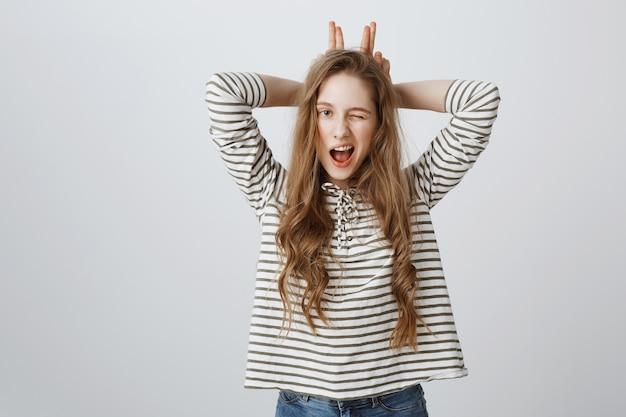 Sassy ładna dziewczyna mruga i pokazuje gest uszy królika