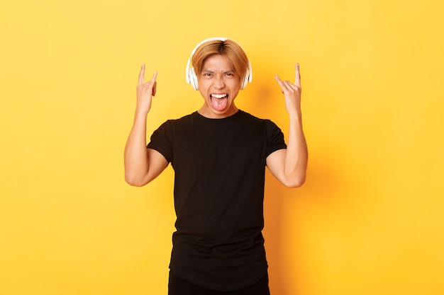 Sassy przystojny azjata lubi heavy metal, słuchanie hard rockowej muzyki, pokazywanie rock-n-rollowych gestów i noszenie bezprzewodowych słuchawek, wystawiony język, stojąca żółta ściana