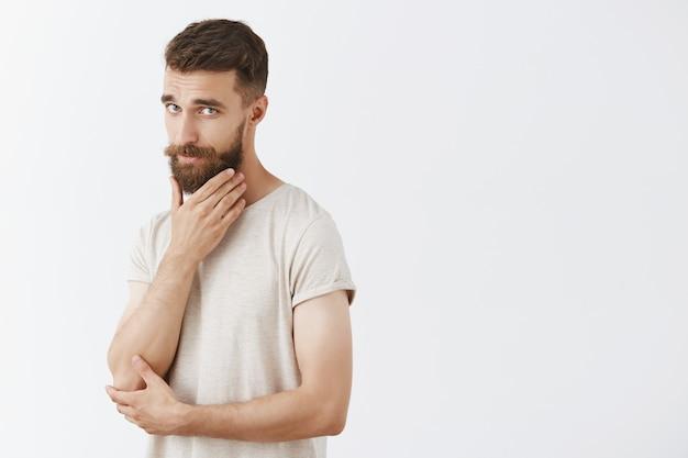 Sassy przystojny brodaty mężczyzna pozuje przy białej ścianie