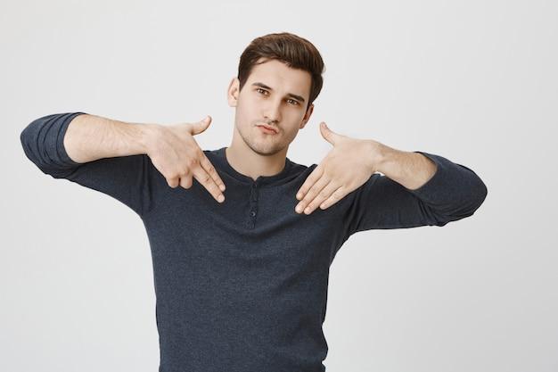 Sassy przystojny facet pokazujący znak broni, zachowujący się fajnie
