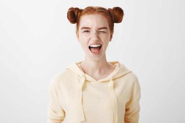 Sassy ruda dziewczyna mruga i uśmiecha się zachęcająco
