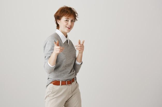 Sassy ruda dziewczyna z krótką fryzurą pozuje na białej ścianie