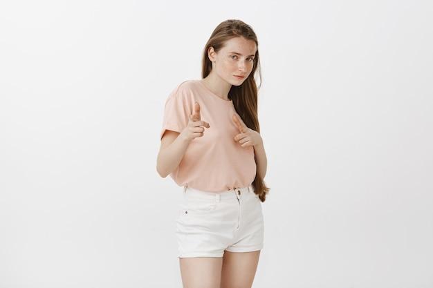 Sassy ruda nastolatka pozuje na białej ścianie