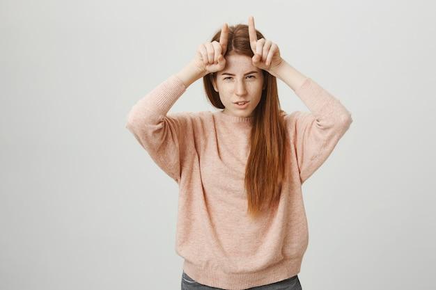 Sassy śliczna ruda dziewczyna pokazująca diabelskie rogi na głowie