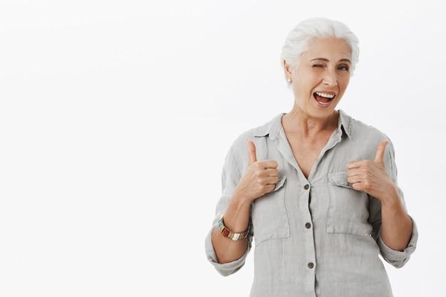 Sassy starsza kobieta mrugająca i uśmiechnięta, pokazująca kciuki w górę z aprobatą, chwaląca dobrą pracę lub komplementy za wspaniały wybór