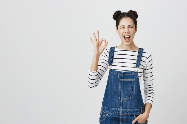 Sassy wesoła dziewczyna z fryzurą bułeczki pokazująca dobry gest i mrugająca, polecam produkt