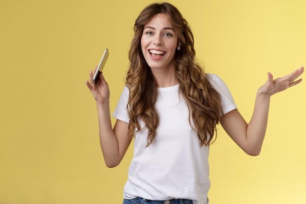Sassy wesoły beztroski atrakcyjna nowoczesna dziewczyna kręcone fryzury zabawy żywy optymistyczny nastrój poruszający się rytm ciała trząść ręce trzymać smartfon synchronizacja warg nosić bezprzewodowe słuchawki douszne słuchać muzyki taniec
