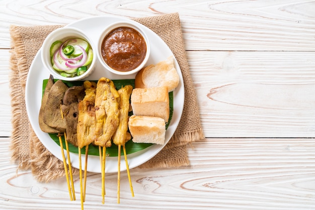 Satay wieprzowe i satay z wątroby z sosem chlebowo-orzechowym i piklami czyli plastrami ogórka i cebulą w occie. azjatycki styl żywności