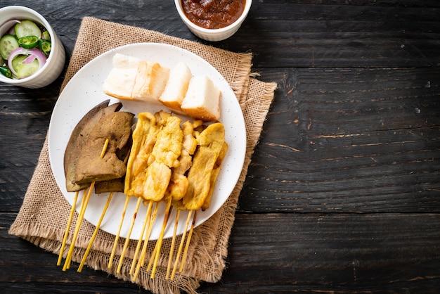 Satay wieprzowe i wątróbkowe satay z chlebem i sosem orzechowym oraz piklami czyli plastrami ogórka i cebulą w occie. azjatycki styl jedzenia