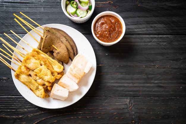 Satay wieprzowe i wątrobowe satay z chlebem i sosem orzechowym oraz piklami, czyli plastrami ogórka i cebulą w occie - azjatyckie jedzenie