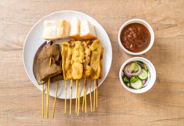 Satay wieprzowe i wątrobowe satay z chlebem i sosem orzechowym oraz piklami, czyli plastrami ogórka i cebulą w occie - kuchnia azjatycka