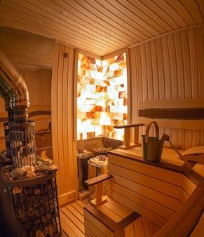 Sauna z drewna ściana kamienna z oświetleniem od wewnątrz klasyczne akcesoria do kąpieli