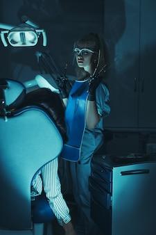 Scena horroru w gabinecie stomatologicznym. szalony zły stomatolog zabił pacjenta na fotelu dentystycznym. szalony maniak, lekarz-morderca.